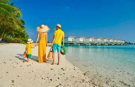 Family on beach, young couple in yellow with three year old boy. Summer vacation at Maldives. 免版税图像