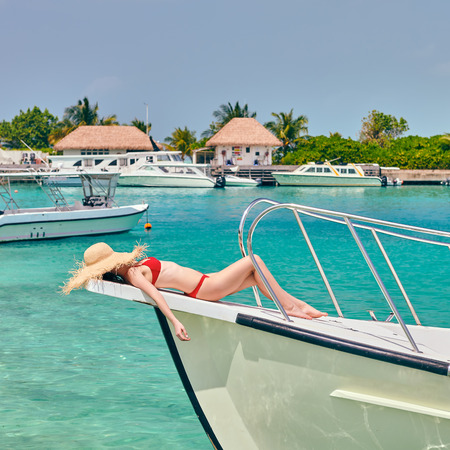Woman in red bikini lying on boat bow. Summer vacation at Maldives.