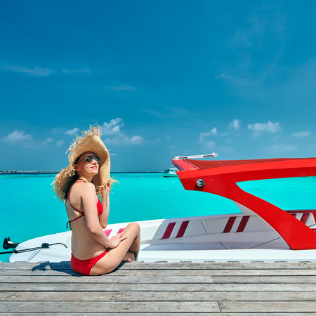 Woman in red bikini sitting on wooden jetty with boat. Summer vacation at Maldives.
