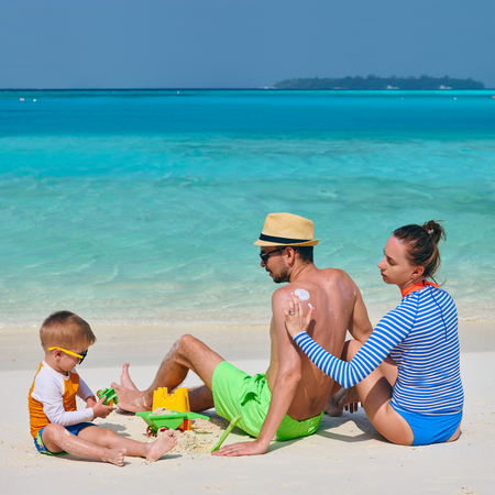 Family on beach, young couple with three year old boy. Woman applying sun screen protection lotion on mans back. Summer vacation at Maldives. Stock Photo