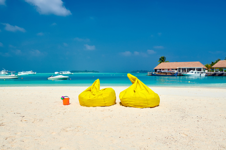 Tropical beach with yellow beanbag chairs. Summer vacation at Maldives.