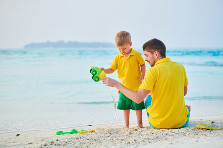 Three year old toddler boy on beach with father. Summer family vacation at Maldives.