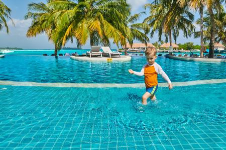 Three year old toddler boy in resort swimming pool. Summer family vacation at Maldives.