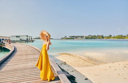 Woman in dress walking on tropical beach boardwalk. Summer vacation at Maldives. 写真素材