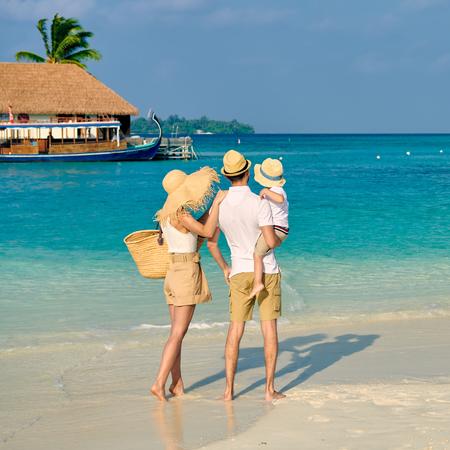 Familie op het strand, jong stel met driejarige jongen. Zomervakantie op de Malediven.