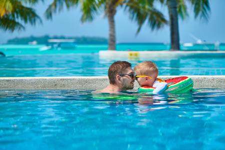 Three year old toddler boy in resort swimming pool eskimo kissing his father. Summer family vacation at Maldives.