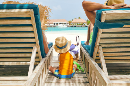 Family at beach on wooden sun bed loungers, young couple with three year old boy. Summer vacation at Maldives. Standard-Bild