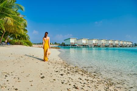 Woman in dress walking on tropical beach. Summer vacation at Maldives.
