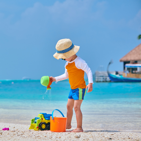 Three year old toddler boy playing with beach toys on beach. Summer family vacation at Maldives. Zdjęcie Seryjne