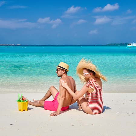 Young couple on beach. Woman applying sun screen protection lotion on man's back. Summer vacation at Maldives. Imagens