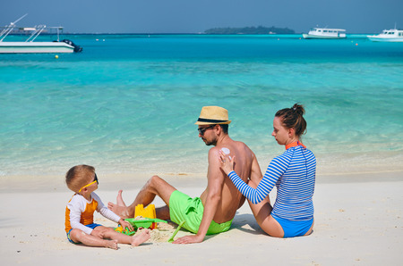 Family on beach, young couple with three year old boy. Woman applying sun screen protection lotion on man's back. Summer vacation at Maldives. Stock Photo