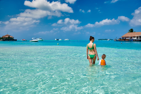 Three year old toddler boy on beach with mother having fun in shallow water. Summer family vacation at Maldives. Stock Photo