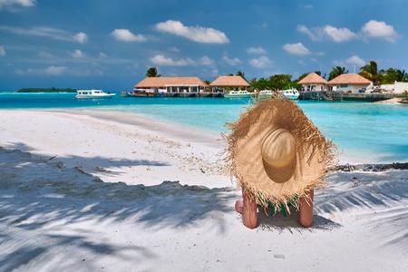 Mujer sentada en la playa bajo la palmera. Vacaciones de verano en Maldivas.