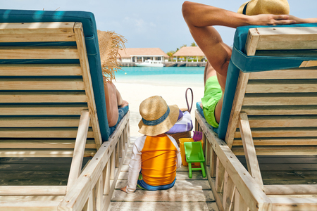 Family at beach on wooden sun bed loungers, young couple with three year old boy. Summer vacation at Maldives. Stock Photo
