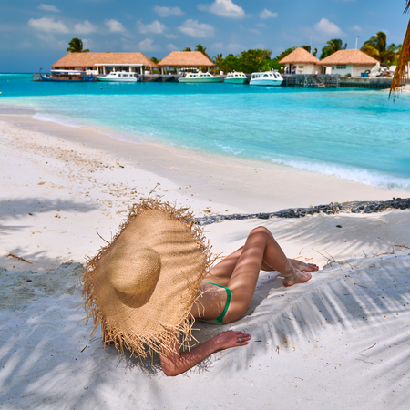 Woman sitting on beach under palm tree. Summer vacation at Maldives.