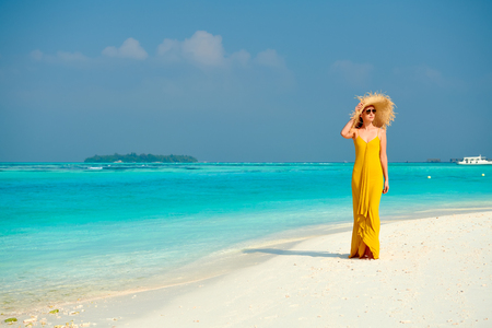Woman in dress walking on tropical beach. Summer vacation at Maldives. Stock Photo
