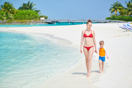 Three year old toddler boy walking on beach with mother. Summer family vacation at Maldives.
