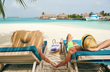 Young couple at beach on wooden sun bed loungers. Summer vacation at Maldives.