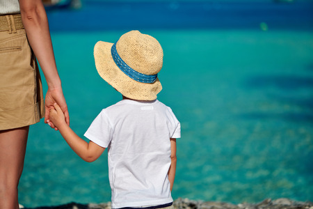 Three year old toddler boy on beach holding mothers hand. Summer family vacation at Maldives.