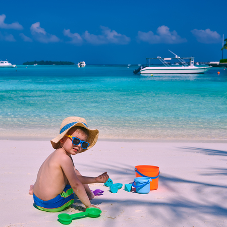 Three year old toddler boy playing with beach toys on beach.  Summer family vacation at Maldives.