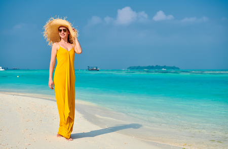 Woman in dress walking on tropical beach. Summer vacation at Maldives. 写真素材