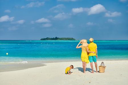 Familia en la playa, pareja joven en amarillo con un niño de tres años. Vacaciones de verano en Maldivas. Foto de archivo