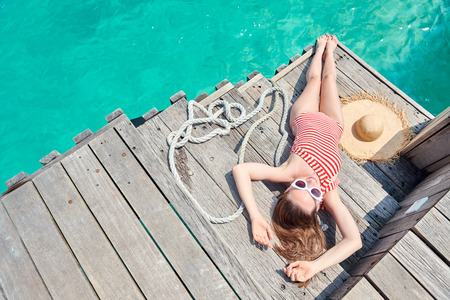 Woman in red striped one-piece swimsuit lying on wooden jetty. Summer vacation at Maldives. Stock Photo