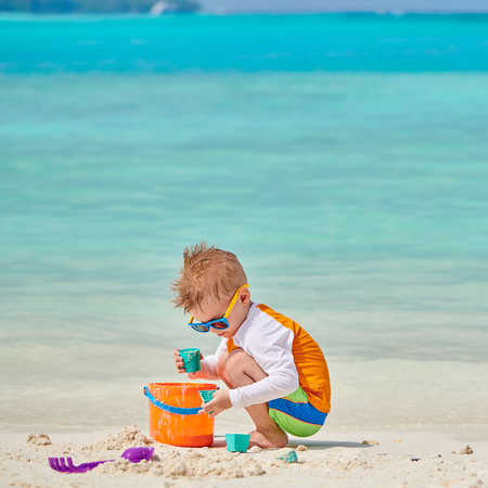 Three year old toddler boy playing with beach toys on beach. Summer family vacation at Maldives. Stock Photo