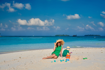 Family on beach, woman in green dress with three year old boy. Summer vacation at Maldives.