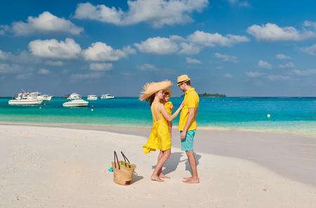 Familie am Strand, junges Paar in Gelb mit drei Jahre altem Jungen. Sommerurlaub auf den Malediven.