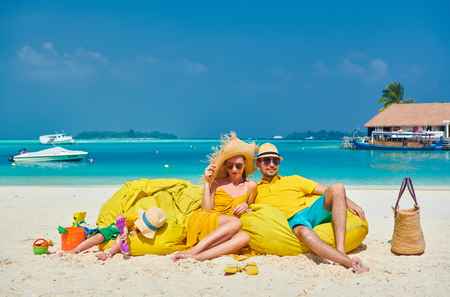 Family on beach, young couple in yellow with three year old boy. Summer vacation at Maldives. Stock Photo