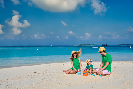 Family on beach, young couple in green with three year old boy. Summer vacation at Maldives.