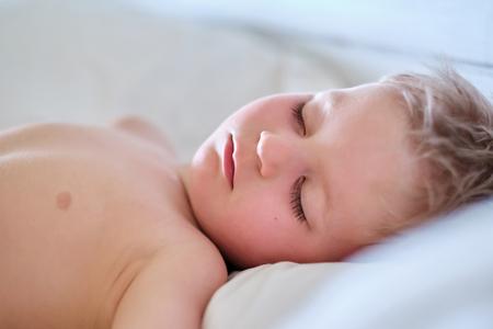 Garçon de trois ans dormant sur l'oreiller