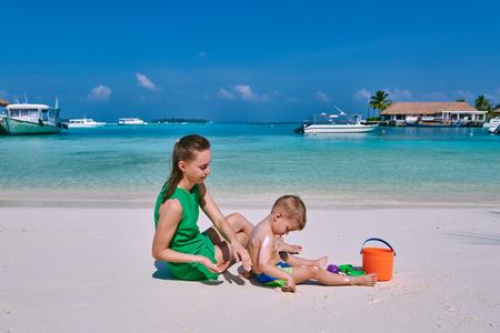 Woman applying sun screen protection lotion on boys back. Summer vacation at Maldives.