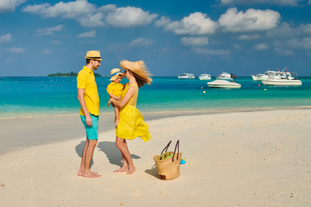 Family on beach, young couple in yellow with three year old boy. Summer vacation at Maldives. 版權商用圖片
