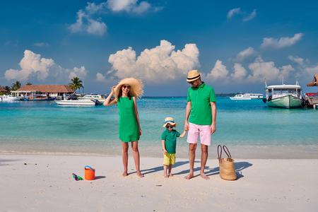 Familia en la playa, pareja joven en verde con un niño de tres años. Vacaciones de verano en Maldivas. Foto de archivo