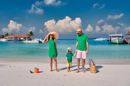 Family on beach, young couple in green with three year old boy. Summer vacation at Maldives. Stock fotó