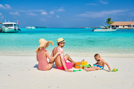 Family on beach, young couple with three year old boy. Woman applying sun screen protection lotion on mans back. Summer vacation at Maldives. 스톡 콘텐츠