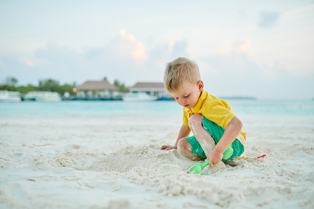 Three year old toddler boy playing with beach toys on beach. Summer family vacation at Maldives. 版權商用圖片