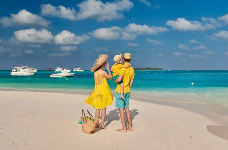 Family on beach, young couple in yellow with three year old boy. Summer vacation at Maldives. Stockfoto