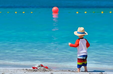 Two year old toddler boy playing with beach toys on beach Stock Photo - 124983695