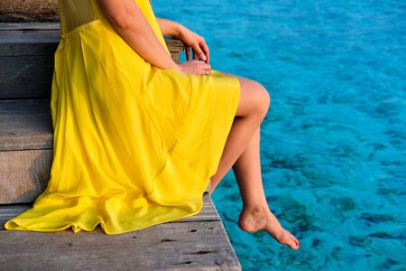 Woman in yellow dress sitting on wooden beach jetty. Summer vacation at Maldives.
