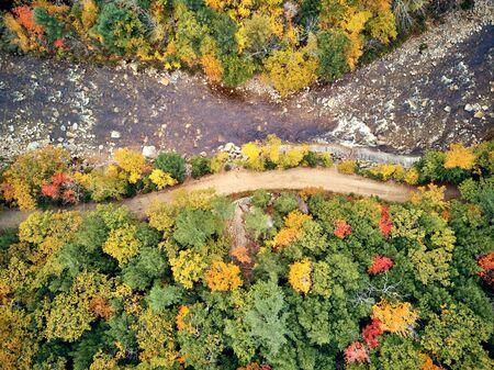 Swift river landscape at autumn in New Hampshire, USA. Fall in New England. Aerial drone shot.