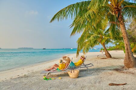 Family on beach, young couple in yellow with three year old boy. Summer vacation at Maldives. Stok Fotoğraf - 124985137