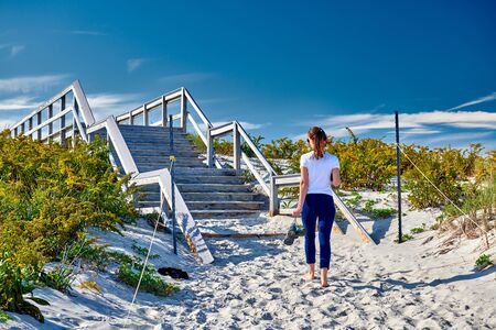 Access trail to Crane beach, Ipswich, Massachusetts, USA. Woman walking to the beach.