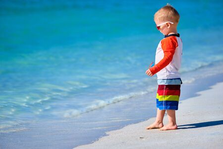 Two year old toddler boy in sunglasses walking on beach