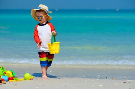 Two year old toddler boy playing with beach toys on beach Stock Photo