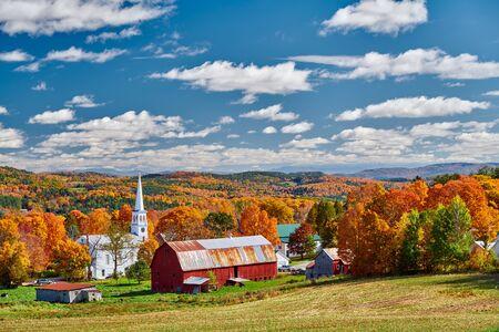 Chiesa congregazionale e fattoria con granaio rosso alla soleggiata giornata autunnale a Peacham, Vermont, USA