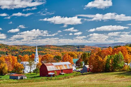Congregational Church and farm with red barn at sunny autumn day in Peacham, Vermont, USA
