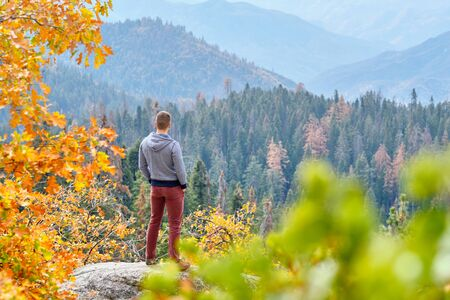 Tourist man hiking in Sequoia National Park at fall, looking at autumn mountain scenic landscape. California, United States.